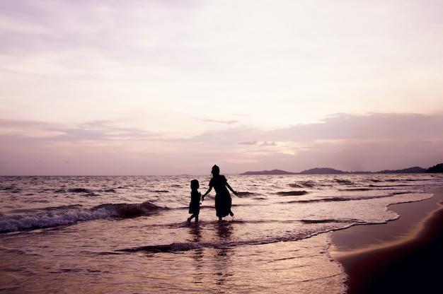 Silhouet van kinderen die op het strand bij zonsondergang spelen