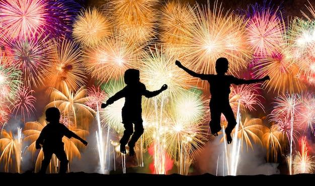 Silhouet van kinderen die over kleurrijk vuurwerk springen