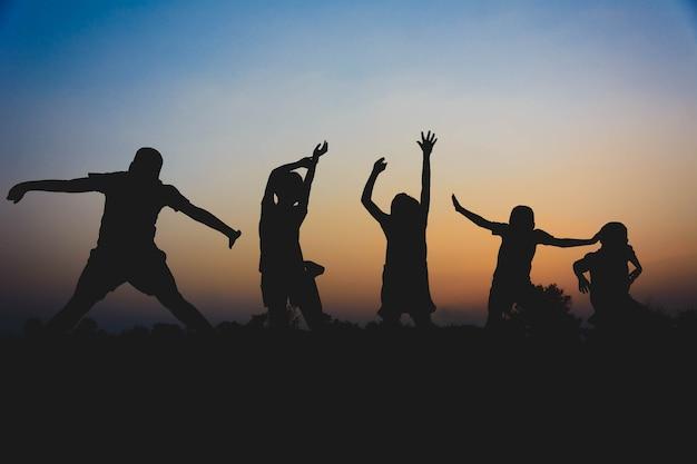 Silhouet van kinderen lopen en genieten in het midden van rijstvelden bij zonsondergang