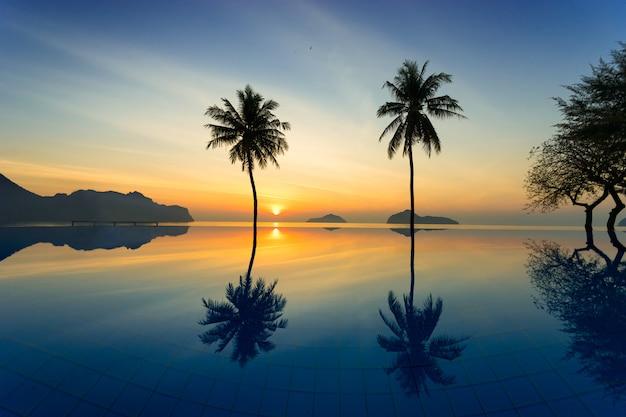 Silhouet van kokospalmen agains zonsopgang weg van het overzees