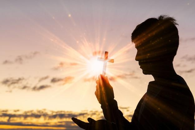 Silhouet van kruis in menselijke hand, de achtergrond is de zonsopgang.