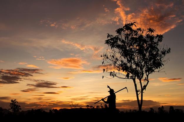 Silhouet van landbouwer die op hemel met zonsondergang in avondtijd richten, landbouwconcept