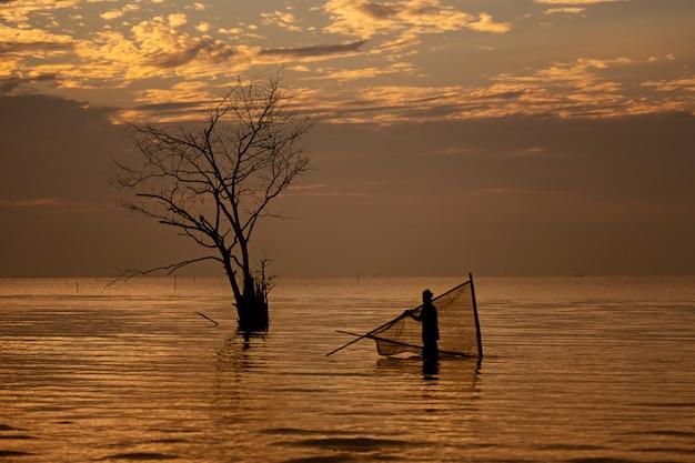 Silhouet van lokale visser die garnalen vinden door traditionele netten te gebruiken bij zonsopgang.