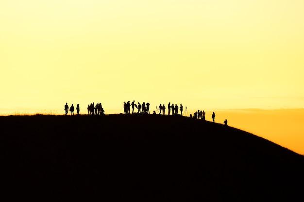 Silhouet van man hand in hand op de top van de berg, succes concept