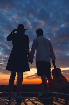 Silhouet van man met gitaar en vrouw in een hoedenstandaard op het dak van een auto op de achtergrond van de zonsondergang