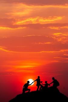 Silhouet van man steekt handen op de top van de berg, succes concept