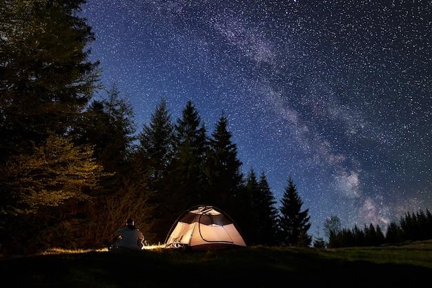 Silhouet van mannelijke wandelaar zit alleen in de buurt van toeristische tent bij kampvuur