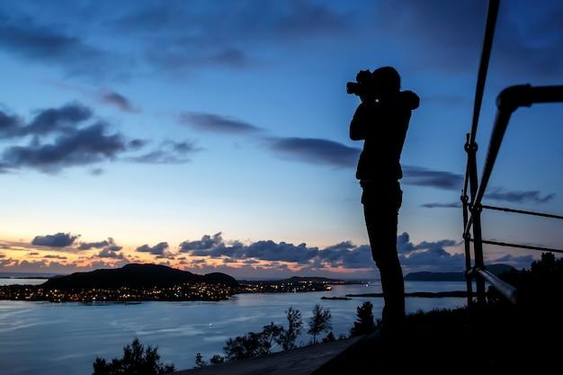 Silhouet van meisje bij zonsopgang in het landschap van noorwegen.