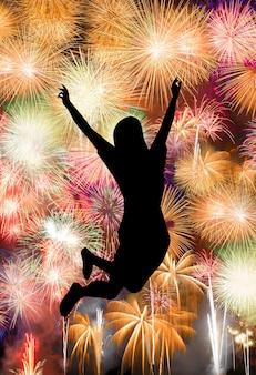 Silhouet van meisje dat gelukkig springt, geniet van fel kleurrijk vuurwerk in de nachtelijke hemel