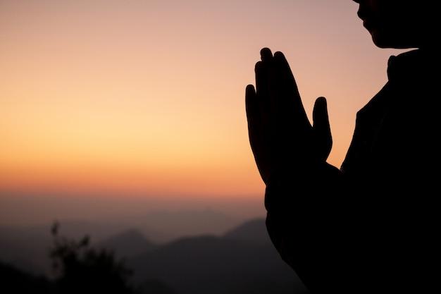Silhouet van meisje die over mooie hemelachtergrond bidden.
