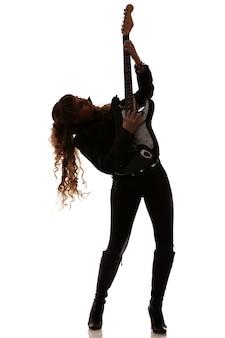 Silhouet van meisje op witte achtergrond met gitaar in de hand, zijwaarts draaien, volledige lengte foto