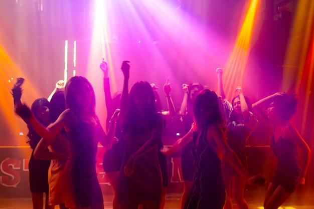Silhouet van mensen dansen in disco nachtclub op muziek van dj op het podium