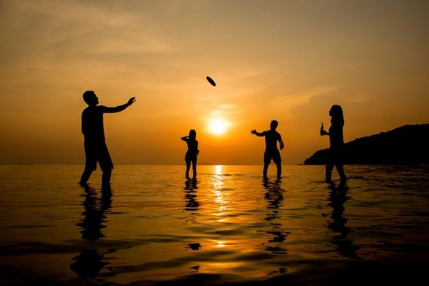 Silhouet van mensen die bij het strand in zonsondergang spelen