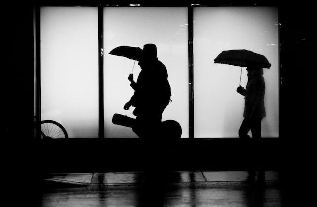 Silhouet van mensen die in de regen lopen met paraplu's en een gitaar in de stad
