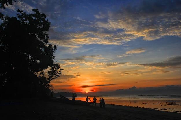 Silhouet van mensen die op het strand spelen