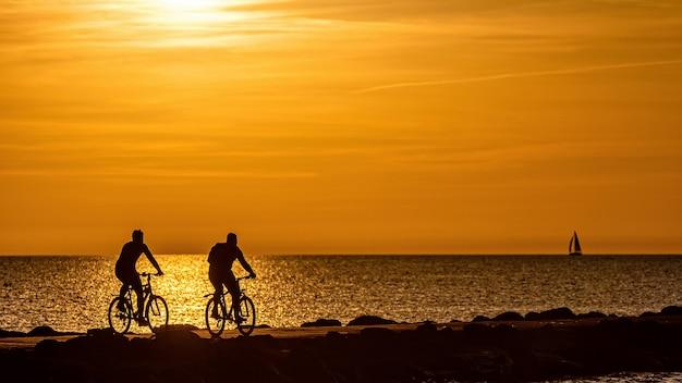 Silhouet van mensen fietsen op de pier tijdens het gouden uur van de zonsondergang