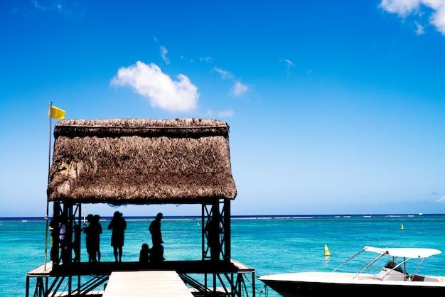 Silhouet van mensen genieten van verborgen voor de zon op zee pier.