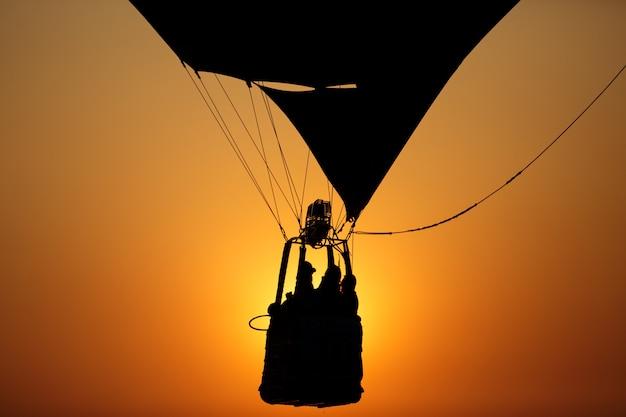 Silhouet van mensen in de mand die van de hete luchtballon in zonsonderganghemel vliegen
