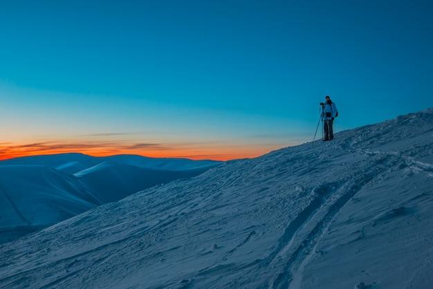 Silhouet van mensenfotograaf die zich op heuvel bevinden en foto van avondvallei en bergen maken bij roze kleurrijke zonsondergang.