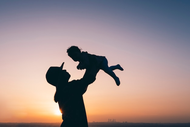 Silhouet van moeder die babymeisje in de lucht opheft