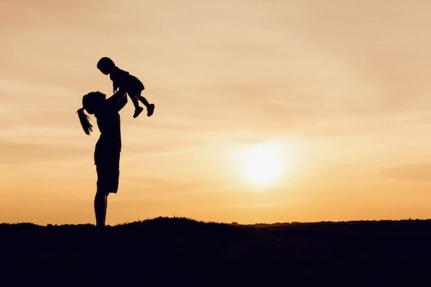 Silhouet van moeder en dochter opheffend kind in lucht over toneelzonsonderganghemel bij rivieroever