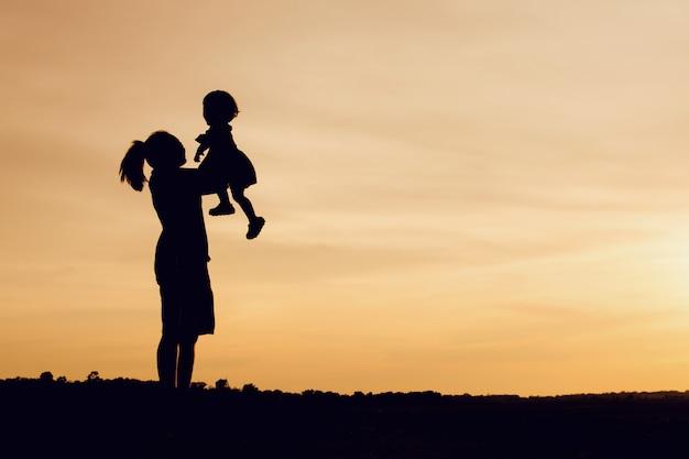 Silhouet van moeder en dochter opheffend kind in lucht over toneelzonsonderganghemel bij rivieroever.