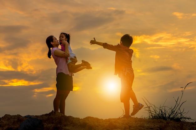 Silhouet van moeder en kind het spelen bij de achtergrond van de gebiedszonsondergang