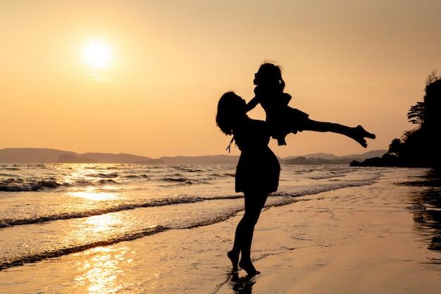 Silhouet van moeder en kind spelen op het strand bij zonsondergang.