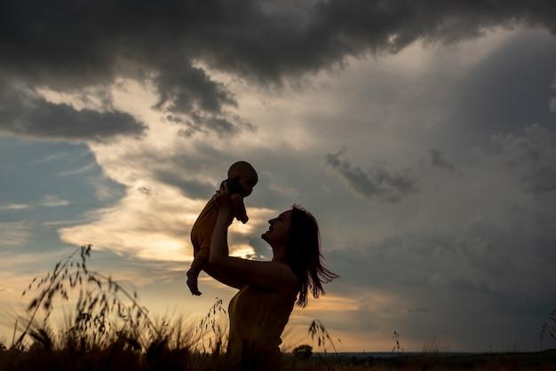 Silhouet van moeder en zoon bij zonsondergang