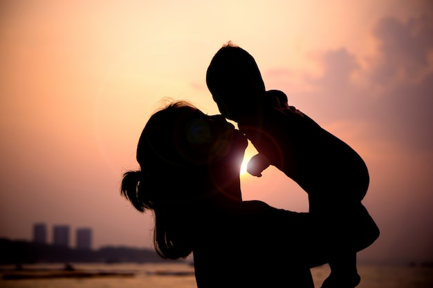 Silhouet van moeder het spelen met haar peuter bij zonsondergang