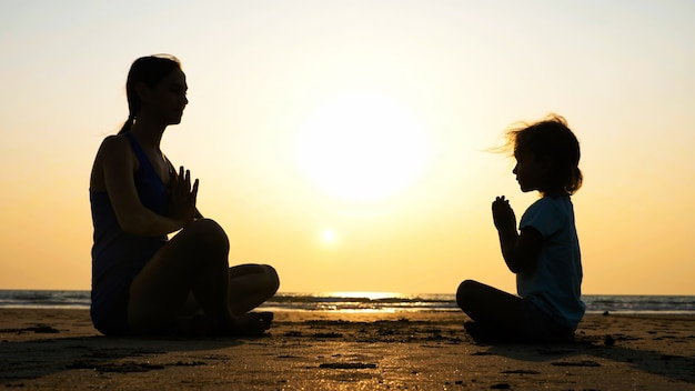 Silhouet van moeder met dochtertje mediteren samen in turkse pose op het strand bij zonsondergang