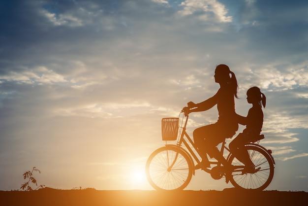 Silhouet van moeder met haar dochter en fiets