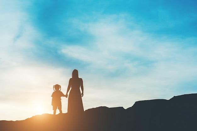Silhouet van moeder met haar dochter status en zonsondergang