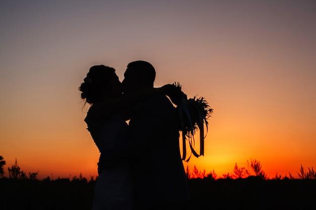 Silhouet van mooi paar verliefd knuffelen buitenshuis op de zonsondergang. silhouet van bruid en bruidegom kussen en knuffelen buitenshuis op zomer oranje zonsondergang. trouwavond. liefdesverhaal concept
