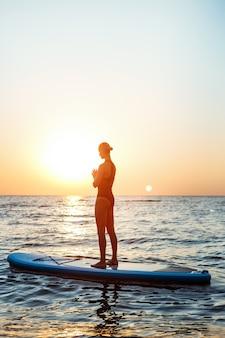Silhouet van mooie vrouw het beoefenen van yoga op surfplank bij zonsopgang.