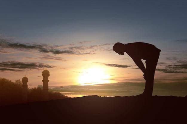 Silhouet van moslim man in biddende positie