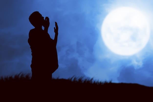 Silhouet van moslim man in ihram kleding staan en bidden terwijl opgeheven armen