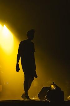 Silhouet van muzikant in een pet met geel achtergrondlicht op rockconcert
