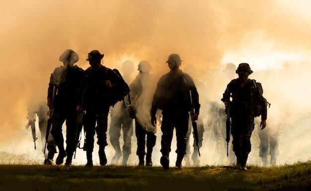 Silhouet van niet-herkende soldaten met geweer lopen door rook