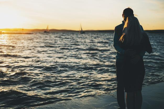 Silhouet van paar in liefde op de pijler, zonsondergangtijd, zeilboten