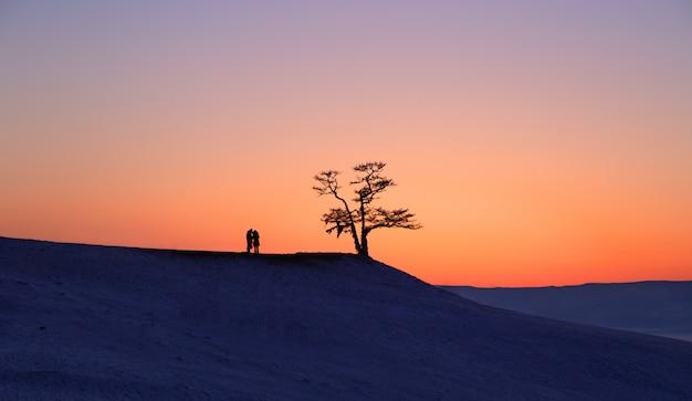 Silhouet van paar onder grote boom in zonsondergang bij meer baikal, olkhon-eiland, siberië in rusland. winter tijd. houd van en ontspan concept
