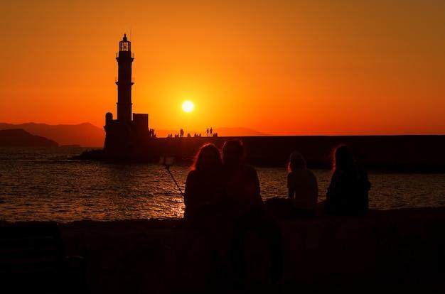Silhouet van paar selfie maken op strand bij zonsondergang in de stad chania