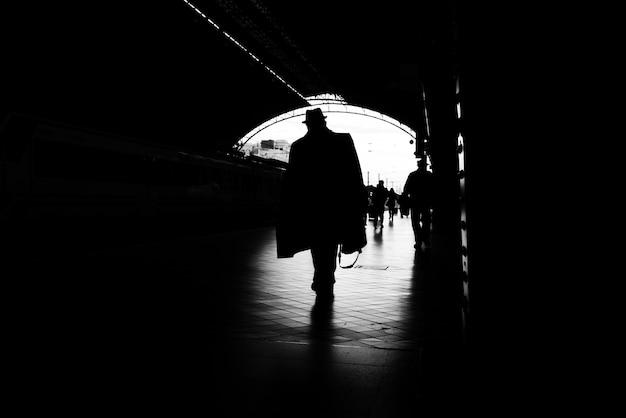 Silhouet van passagiers in een treinstation.