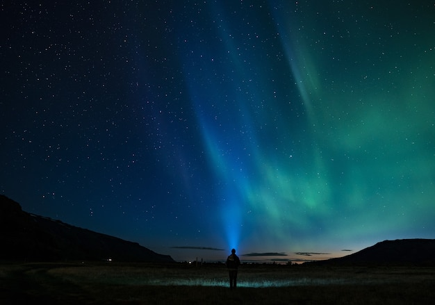 Silhouet van persoon die zich onder aurora nachtelijke hemel bevindt