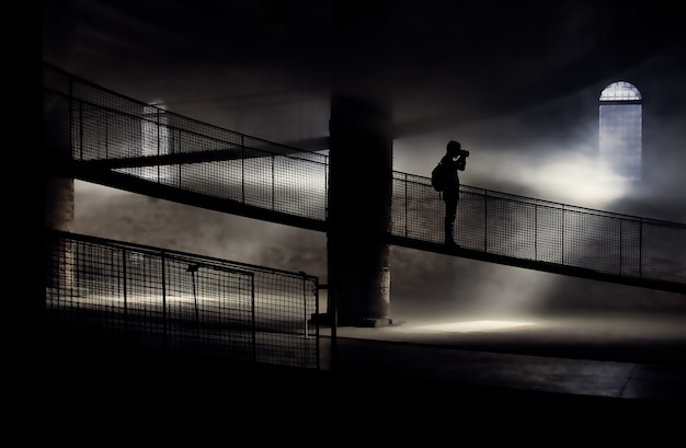 Silhouet van persoon die zich op brug bevindt tijdens het nemen van foto
