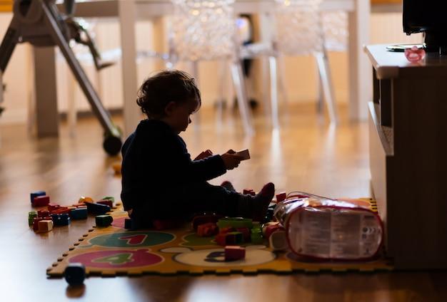 Silhouet van peuter die met speelgoed thuis betaalt.