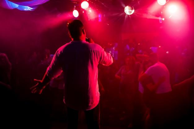 Silhouet van presentator met microfoon in de hand op het podium bij concert in nachtclub