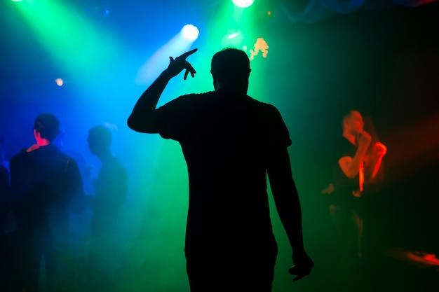 Silhouet van presentator op het stadium van de nachtclub bij overleg terug bij het evenement