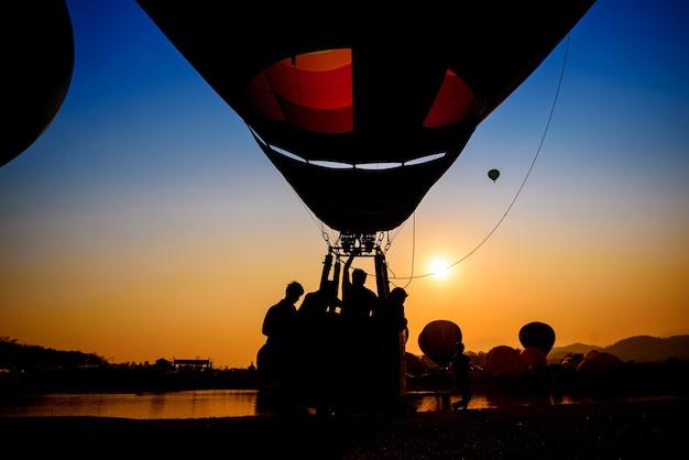Silhouet van reiziger in de mand van de hete luchtballon bij avondrood