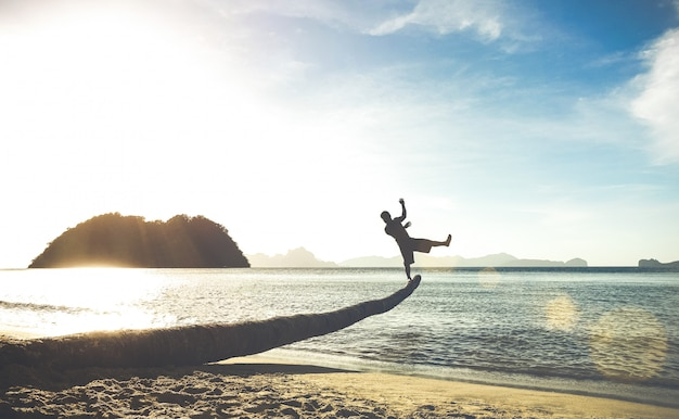 Silhouet van reizigerskerel op grappige sprong van palm